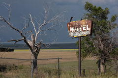 Rusty Old Motel Sign and Tree. Rusty old motel sign with bullet holes next to an old tree, with a storm in the background, in eastern Colorado Royalty Free Stock Photography