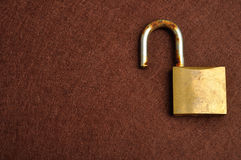 A rusty old pad lock. Displayed on a brown background Royalty Free Stock Photo