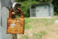 Rusty old padlock with building in background Royalty Free Stock Photo