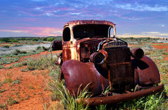A rusty old pick-up truck sits derelict in a field. An old pick up truck sitting and  rusting in a field Royalty Free Stock Photo