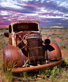 A rusty old pick-up truck sits derelict in a field. An old pick up truck sitting and  rusting in a field Royalty Free Stock Images