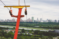Rusty old red yellow ski lift against the backdrop of the Moscow city. With copyspace Stock Photos