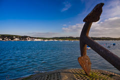 Rusty old ships anchor. Ships anchor at end of pier overlooking sea and marine harbour Royalty Free Stock Images
