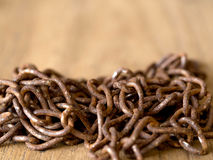 Rusty old steel chain put on a wooden table. Stock Images