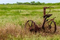 Rusty Old Texas Metal Farm utrustning i fält Arkivbilder