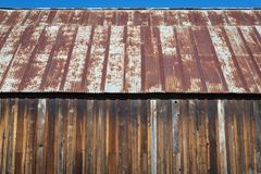 Rusty old tin roof. Old wooden building with rusty metal tin roof royalty free stock photo