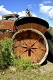 Rusty old tractor in a junkyard. A very old rusty tractor with a huge fender is missing a tire on the rim in a salvage junkyard Royalty Free Stock Photo