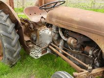 A rusty old tractor sitting in a grass area in England royalty free stock photography
