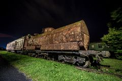 Rusty old train wagon at night. Decayed locomotive car at night Stock Photos
