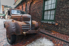 Rusty old truck at the Distillery Toronto. Old rusty truck parked beside the brick walled building stock photos