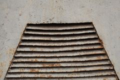 Rusty old ventilation grille on metal wall painted in gray. Color Stock Photos