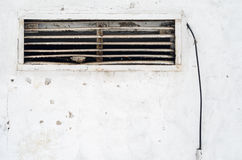 Rusty old ventilation grille in the wall with a wire. Old ragged plaster white Stock Photo