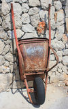 Rusty old wheelbarrow. On stony wall background - resting in the sun Royalty Free Stock Images