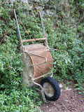 Rusty old wheelbarrow against wall, plants. Stock Images