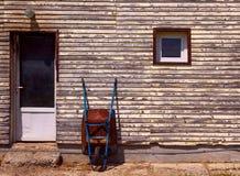 Rusty old wheelbarrow leaning against wall Royalty Free Stock Photo