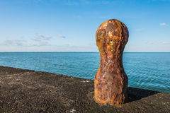 Rusty orange colored iron bollard from close Royalty Free Stock Image