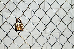 Rusty padlock. Rusty obsolete padlock on the wired fence royalty free stock image