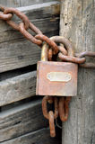 Rusty padlock. A rusty padlock attached to a metal chain locking a wooden door Stock Images