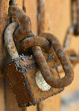 Rusty padlock. A rusty padlock attached to a metal gate and chain royalty free stock photo