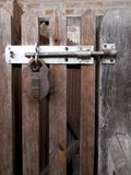 Padlock clasp and hasp. Rusty padlock clasp and staple securing timber gate to side of residential building royalty free stock photo