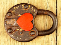 Rusty padlock and heart on a wooden background. Stock Photos