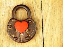 Rusty padlock and heart on a wooden background. Royalty Free Stock Image
