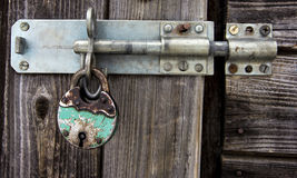 Rusty padlock and latch on old wooden door Stock Image