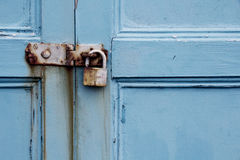 Rusty padlock on old painted wooden door Royalty Free Stock Photography