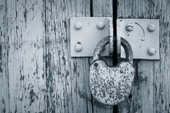 Rusty padlock on an old painted wooden gate Royalty Free Stock Image