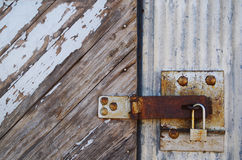 Rusty padlock on old wooden door. Rusty padlock and hasp on a wooden door of an abandoned warehouse Royalty Free Stock Photo