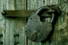 A rusty padlock on an old wooden door. Stock Photo