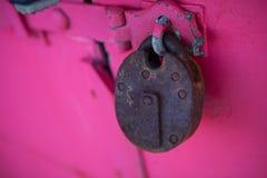 Rusty padlock on pink background. Old rusty padlock on vibrant pink background Royalty Free Stock Photo