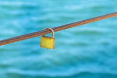 Rusty Padlock que pendura em um fio do ferro no fundo da água do mar fotografia de stock royalty free