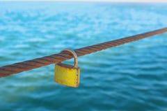 Rusty Padlock que pendura em um fio do ferro no fundo da água do mar imagens de stock