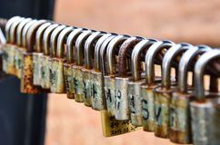 Rusty padlocks on the chain. Rusty padlocks with different alphabets hanging on the chain Royalty Free Stock Image