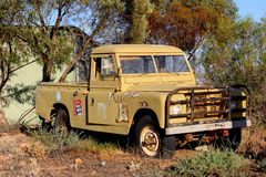 Retro pickup truck stickers Carlton beer, Australia. An abandoned rusty pick up car wreck with advertisement sign boards of Carlton Mid beer in the mining town stock image