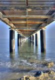Rusty Pier  on the ocean  from below. Rusty metallic  pier from sea level in vertical composition creating a diagonal directive tunnel Royalty Free Stock Images