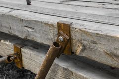 Rusty pipe bolted to the board with nut. Is close royalty free stock images