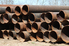 The rusty Pipes of large diameter stored on the ground. Stock Photo