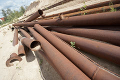 Rusty pipes left in field. With sand Stock Image