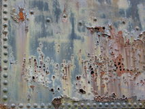 Rusty, Pitted Metal. A metal riveted panel is marked by rust and pits Stock Photography
