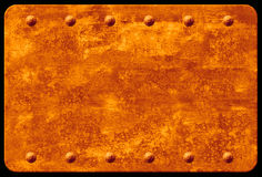 Rusty Plaque with Rivets. A rusted metal plaque with rows of rivets at top and bottom Stock Photo
