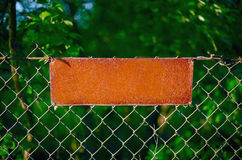 The rusty plate on the metal gauze of a fencing. Empty metal plate - a sign on the fence Stock Photography