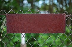 Rusty Plate on a metal grating. Rusty metal plate-worn sign on the fence Royalty Free Stock Image