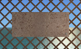 Rusty plate with the sea. Sunny sea viewed through metal grid with a rusty plate attached. Rendered 3d design Stock Images