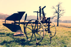 Rusty plow in the field, Vintage filter Royalty Free Stock Photography