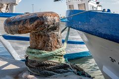 Rusty Pollard with rope in the Harbour with blue ship in the background stock photo