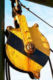 Rusty pulley wheel, painted in yellow black warning colors stock photography