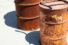 Rusty and punctured steel drums. Two rusty steel drums with one showing a puncture hole stock photo