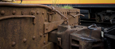Rusty Railroad car and hitch with grass growing out of the top Stock Photo